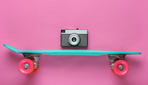 Estilo retrô. mini placa cruiser de plástico e câmera retro. tendência de cor pastel. diversão de verão. conceito minimalista da juventude. anos 80. vista do topo