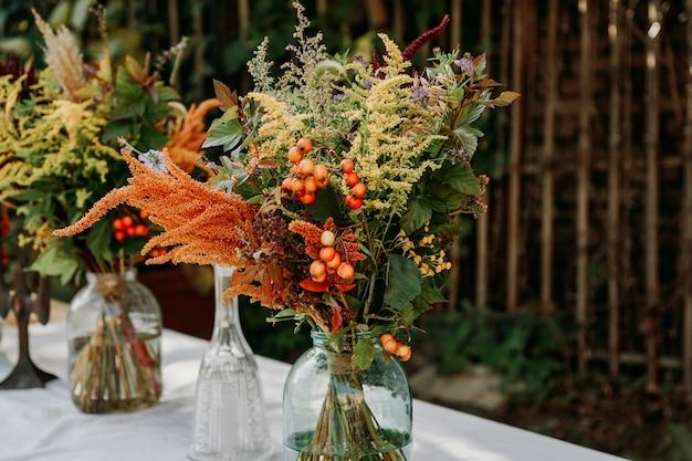 Estilo rústico. buquês de estilo boho na mesa em vasos e potes de vidro. mesa de madeira e toalha de mesa branca