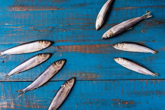 Estilo rústico. padrão de peixe. arenque peixe em um velho fundo de madeira azul