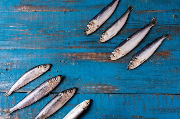 Estilo rústico. padrão de peixe. os peixes dos arenques em um fundo de madeira azul velho, configuração lisa, copiam o espaço.