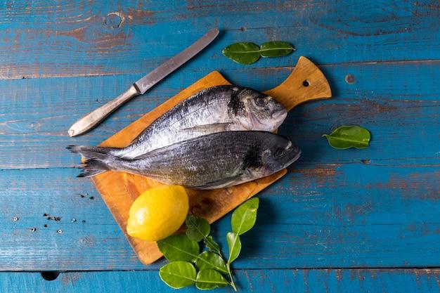 Estilo rústico. seabass peixe em um velho fundo azul de madeira, limão e faca de cozinha, antes de cozinhar