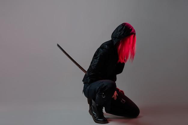 Estilo techno cyber punk, lutador ninja futurista, jovem com cabelo rosa em um capuz preto usa uma katana, foto de estúdio em cinza