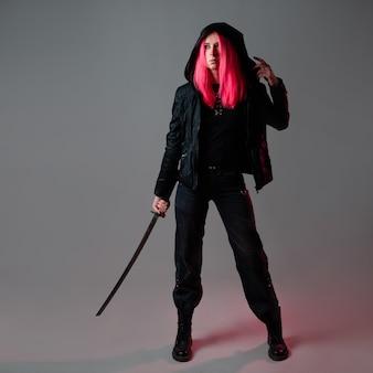 Estilo techno cyber punk, ninja futurista, jovem com cabelo rosa em roupas pretas com uma katana, foto de estúdio em cinza