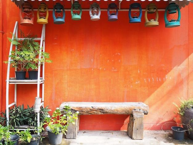 Estilo vintage de decoração de jardim tropical colorido com espaço de cópia. banco de madeira velho e vasos de flores com lâmpadas coloridas retrô pairando sobre a parede de concreto laranja grunge.