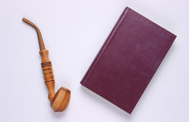 Estilo vintage. livro antigo, fumar cachimbo em branco