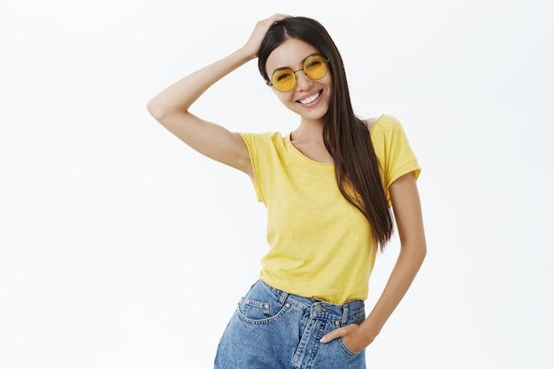 Estilosa charmosa e despreocupada fotógrafa freelance com óculos de sol da moda e camiseta amarela tocando o cabelo