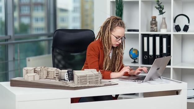 Estilosa engenheira trabalha na agência de projetos com um laptop e examina a maquete do futuro residencial