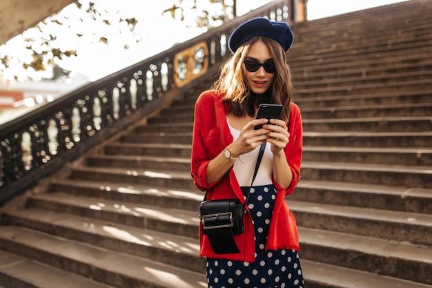 Estilosa jovem parisiense com cabelo castanho ondulado, boina, óculos escuros pretos, top branco, saia de bolinhas e camisa vermelha, procurando algo no telefone ao ar livre