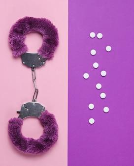 Estimulação sexual. algemas para jogos sexuais com pílulas em fundo rosa roxo. brinquedo bdsm sexual. fetiche, conceito erótico. vista do topo