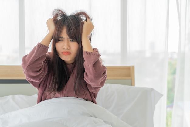 Estirpe asiática da mulher e sério na cama