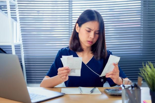Estirpe o rosto mão de mulher asiática segurando a conta de despesas e cálculo mensal sobre as contas da dívida à mesa no escritório em casa.