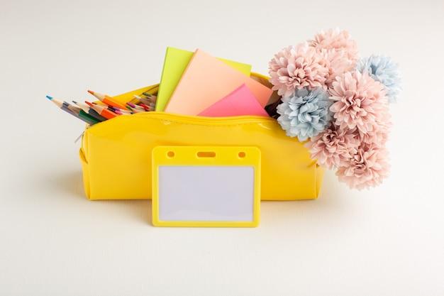 Estojo amarelo frontal com flores coloridas a lápis e adesivos na superfície branca
