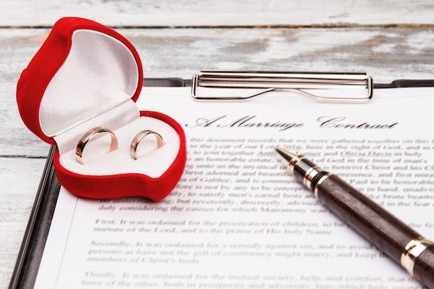 Estojo com anéis de casamento. contrato de casamento e caneta.