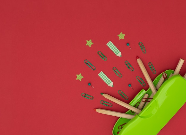 Estojo verde, lápis de madeira, clipes e alfinetes vermelhos e verdes, lápis e adesivos em forma de estrela