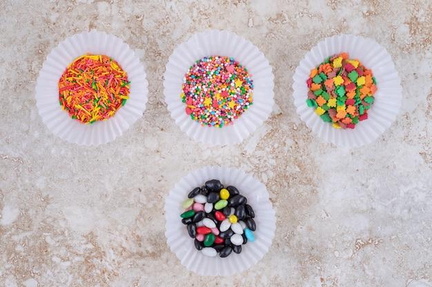 Estojos de patty com pequenas pilhas de doces