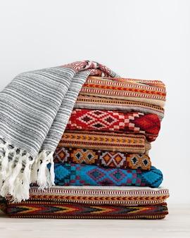 Estolas de tapetes quentes são empilhadas em várias fileiras. acessórios para o frio