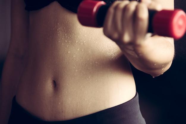 Estômago da barriga desportiva suado da mulher modelo lady da aptidão após o exercício pesado, treino de menina de escritório suando com conceito de perda de peso do haltere.