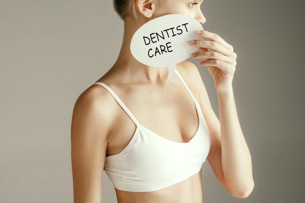 Estomatologia, dentista, odontologia, saúde, clareamento, conceito médico. cabeça e ombros de mulher segurando wods cuidados dentários