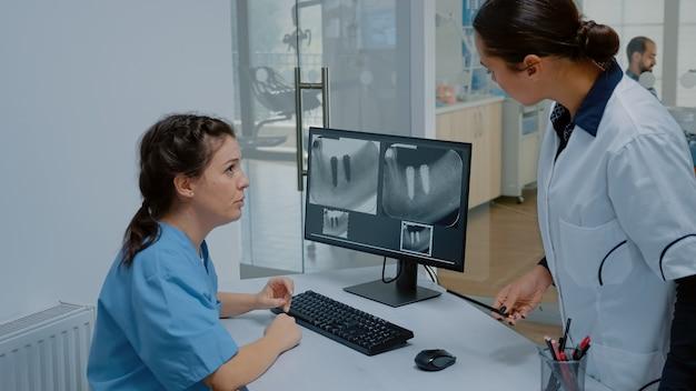Estomatologista e enfermeira examinando radiografia dentária