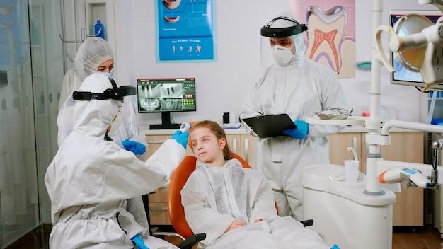 Estomatologista em traje de proteção medindo a temperatura do paciente infantil antes do exame odontológico durante a pandemia de coronavírus. enfermeira de macacão e máscara interrogando mulher e fazendo anotações na prancheta