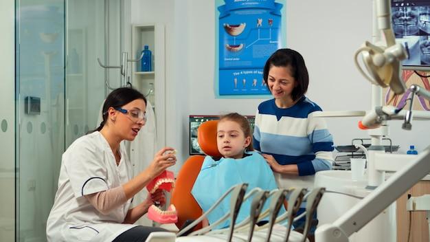 Estomatologista explicando a higiene dental adequada usando o esqueleto dos dentes de apresentação, extraindo uma massa dele. dentista dizendo para brincar com o procedimento, segurando uma amostra de mandíbula humana no escritório de estomatologia.