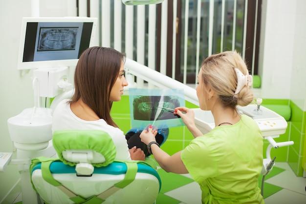 Estomatologista fêmea nas luvas protetoras que examinam os dentes do paciente.