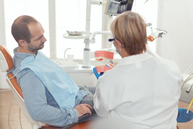 Estomatologista segurando modelo sanitário de mandíbula conversando com homem doente