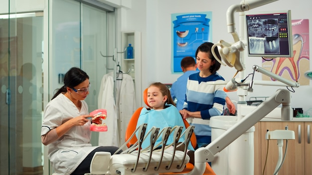 Estomatologista segurando o modelo de gesso da mandíbula, falando com a paciente do sexo feminino. dentista mostrando a higiene dental correta usando mock-up de esqueleto de dentes, amostra de mandíbula humana com escova de dentes