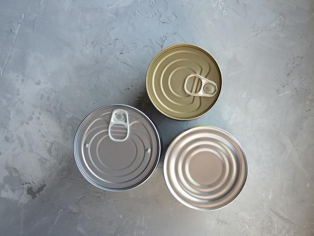 Estoque de crise de suprimentos de alimentos para o período de isolamento de quarentena. vários alimentos enlatados em latas em fundo cinza de concreto. alimentos não perecíveis e de longa duração para sobrevivência em condições de emergência.