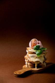 Estoque de queijo derretido torrado, sanduíches prensados com carne de presunto, folhas de manjericão em uma tábua de madeira sobre a parede marrom escura