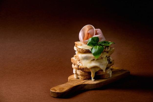 Estoque de queijo derretido torrado, sanduíches prensados com carne de presunto, folhas de manjericão em uma tábua de madeira sobre fundo marrom escuro