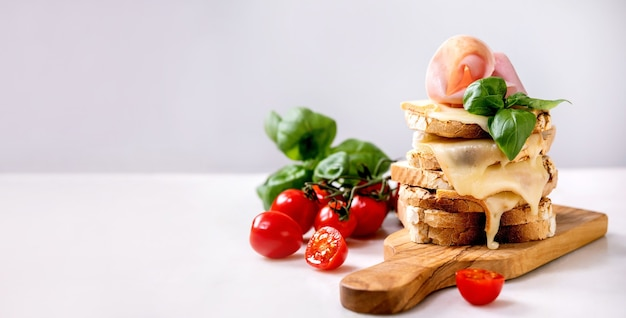 Estoque de queijo derretido torrado, sanduíches prensados com carne de presunto, tomate cereja e folhas de manjericão em uma tábua de madeira na mesa de mármore branco.
