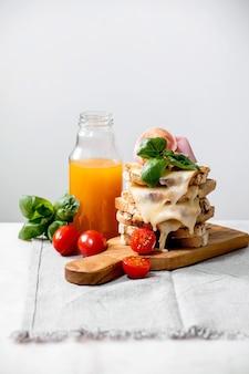 Estoque de queijo derretido torrado, sanduíches prensados com carne de presunto, tomate cereja, suco de laranja e folhas de manjericão em uma tábua de madeira na mesa de mármore branco