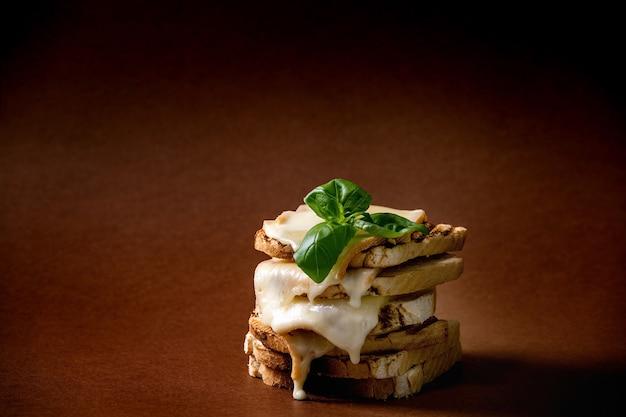 Estoque de queijo derretido torrado, sanduíches prensados com folhas de manjericão sobre fundo marrom escuro