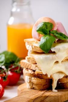 Estoque de sanduíches de queijo derretido torrado com presunto, tomate cereja, suco de laranja e folhas de manjericão em uma tábua de madeira. fechar-se