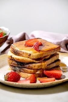 Estoque de torradas francesas com morangos frescos e xarope de bordo mergulhado na placa de cerâmica e guardanapo de pano rosa sobre a mesa branca. café da manhã em casa