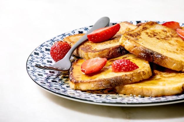 Estoque de torradas francesas com morangos frescos e xarope de bordo na placa de cerâmica com garfo na mesa de mármore branco. fechar-se