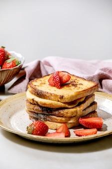 Estoque de torradas francesas com morangos frescos em um prato de cerâmica e um guardanapo de pano rosa sobre a mesa branca