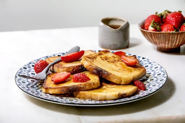 Estoque de torradas francesas com morangos frescos na placa de cerâmica, xarope de bordo no jarro de cerâmica e garfo sobre a mesa de mármore branco. copie o espaço