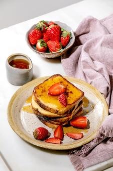 Estoque de torradas francesas com morangos frescos na placa de cerâmica, xarope de bordo no jarro de cerâmica e guardanapo de pano rosa sobre a mesa branca. café da manhã em casa