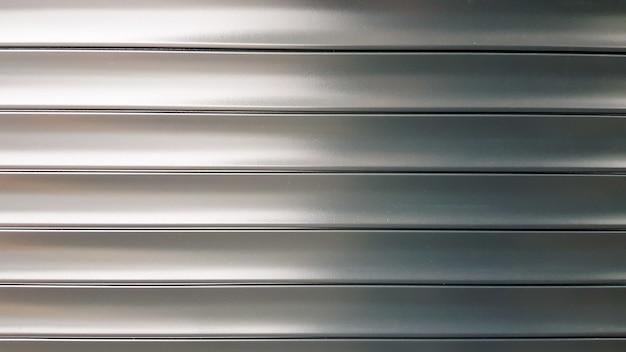 Estores em textura ou roleta. persianas metálicas horizontais com portões fechados prateados listrados. fundo do sumário da textura do metal de alumínio.