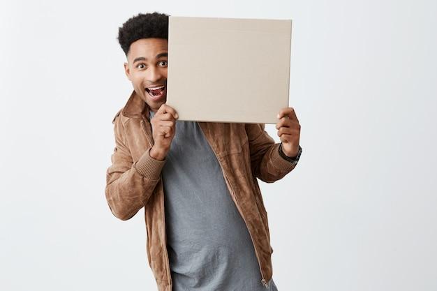 Estou aqui. emoções positivas. copie o espaço para propaganda. feche de jovem afro-americano bonito com cabelo escuro encaracolado em roupas casuais de outono, olhando para a câmera da placa da caixa.