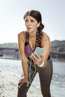 Estou cansado. mulher simpática e simpática segurando o telefone enquanto se sente ao correr