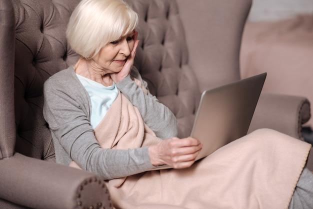 Estou chocado. vista lateral de uma mulher muito idosa sentada no sofá com o cobertor e olhando de forma impressionante para a tela do laptop.