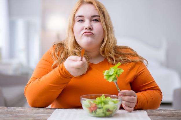 Estou determinado. mulher séria e robusta sentada à mesa e tomando café da manhã saudável