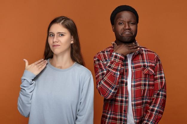 Estou farto. irritada e descontente, jovem de aparência europeia posando isolada com seu namorado africano, ambos mostrando gestos no pescoço, dizendo para cortá-lo. comunicação não verbal