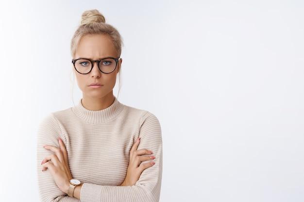 Estou louco por você. retrato de uma mulher loira fofa mal-humorada e infantil com óculos de penteado coque cruzando os braços sobre o peito, temperamental e agressiva, carrancuda e carrancuda, sentindo raiva por uma parede branca