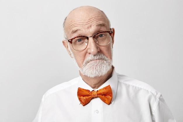 Estou muito impressionado. idoso europeu com a barba por fazer emocional, aposentado, usando óculos e gravata borboleta