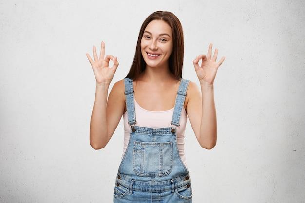 Estou ótimo. alegria e felicidade. imagens de feliz fêmea jovem feliz sorrindo amplamente e fazendo okey gesto com ambas as mãos, regozijando-se em bom dia, objetivos de vida ou realizações. linguagem corporal