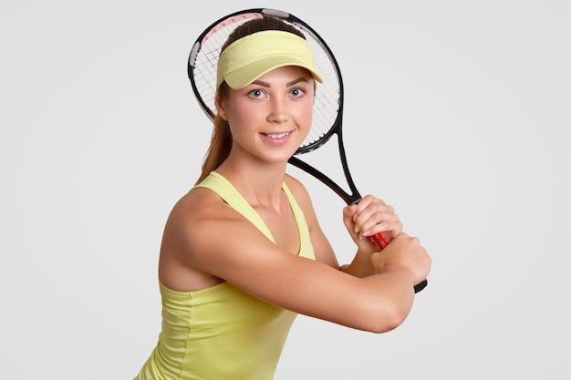 Estou pronto para jogar! o tampão ativo saudável bonito da mulher no tribunal, camisa ocasional de t, guarda a raquete de tênis, olha positivamente diretamente na câmera, isolada sobre a parede branca. pessoas, conceito de hobby